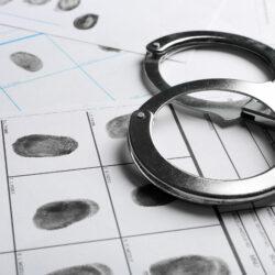 Handcuffs and fingerprint record sheets, closeup. Criminal investigation